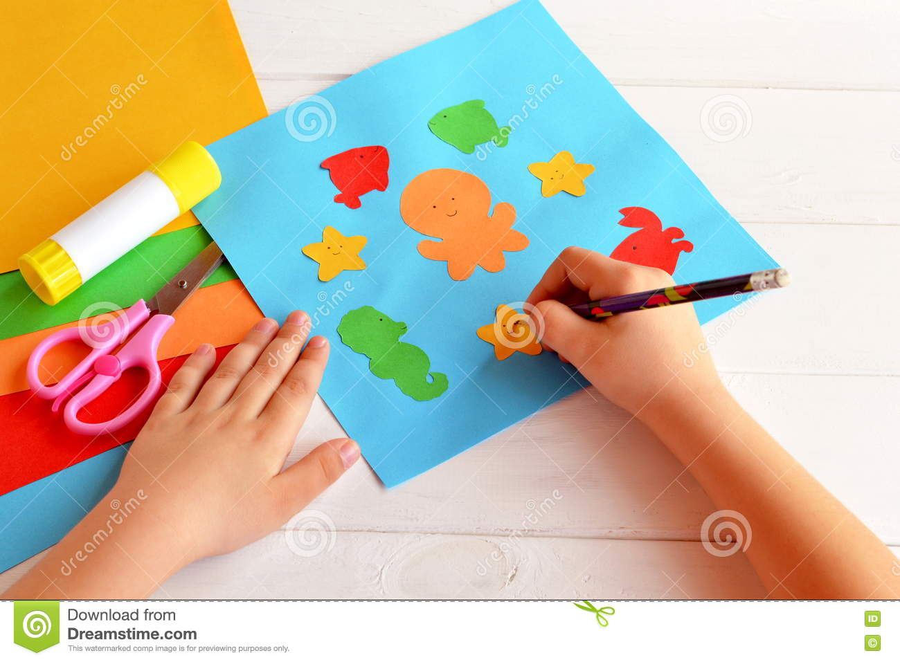 Child Holds A Pencil And Draws Sheets Of Colored Paper Scissors Glue Set For Kids Art Stock