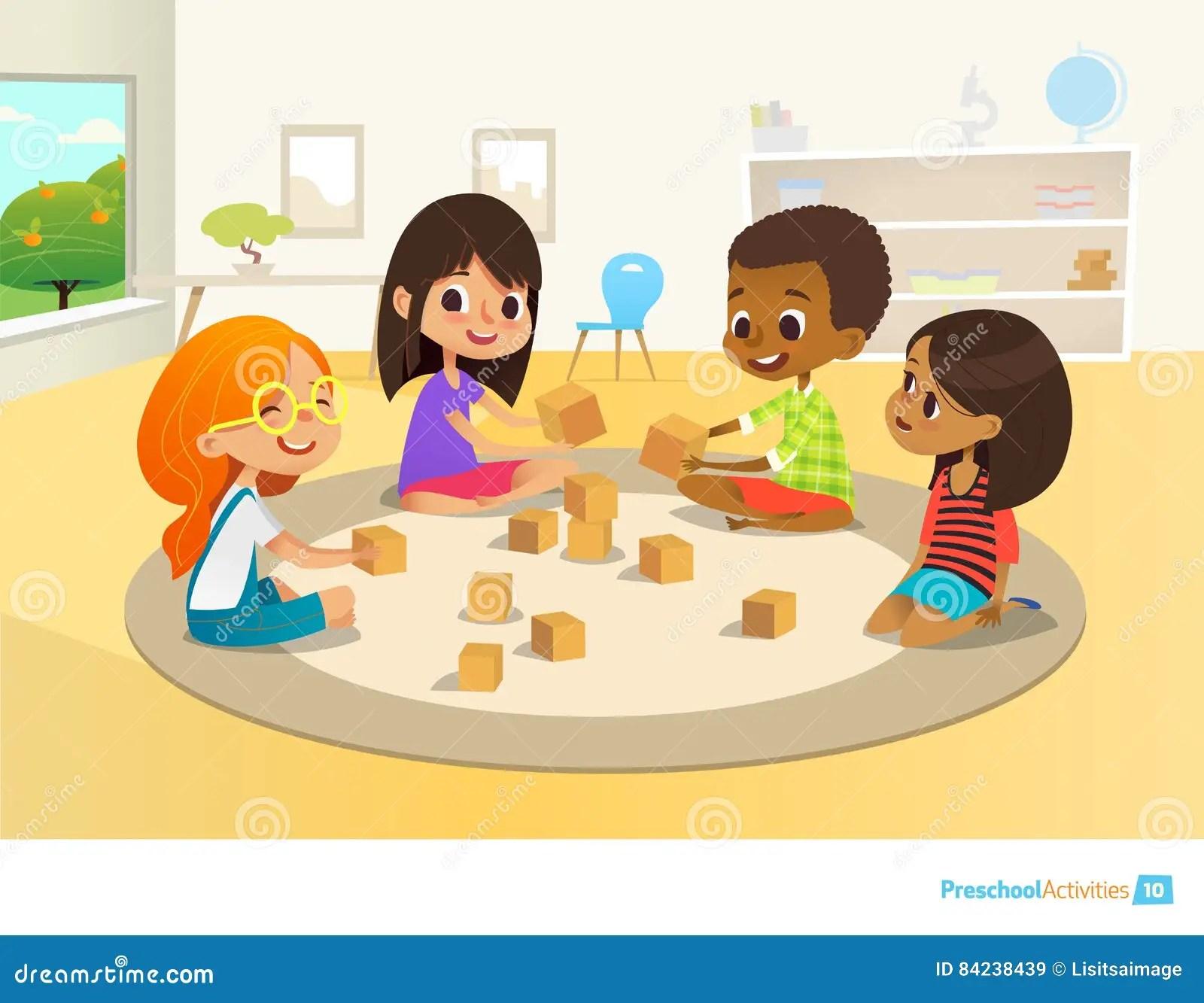 Children Sit In Circle On Round Carpet In Kindergarten