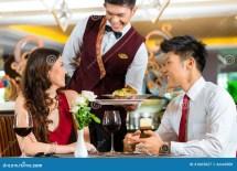 Chinese Waiter Serving Dinner In Elegant Restaurant