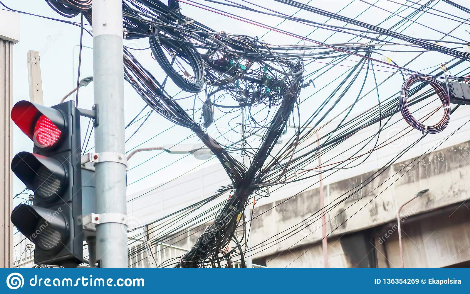hight resolution of closeup on communication wire and internet junction telephone wire and electricity power line messy intersection with traffic light in bangkok thailand