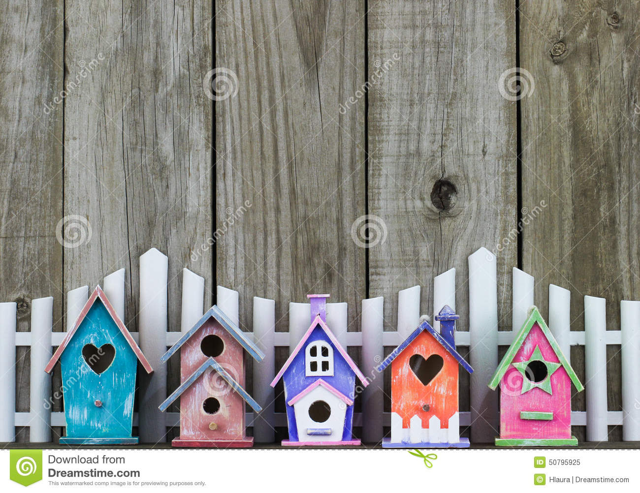 Colorful Birdhouses By White Picket Fence Stock Photo