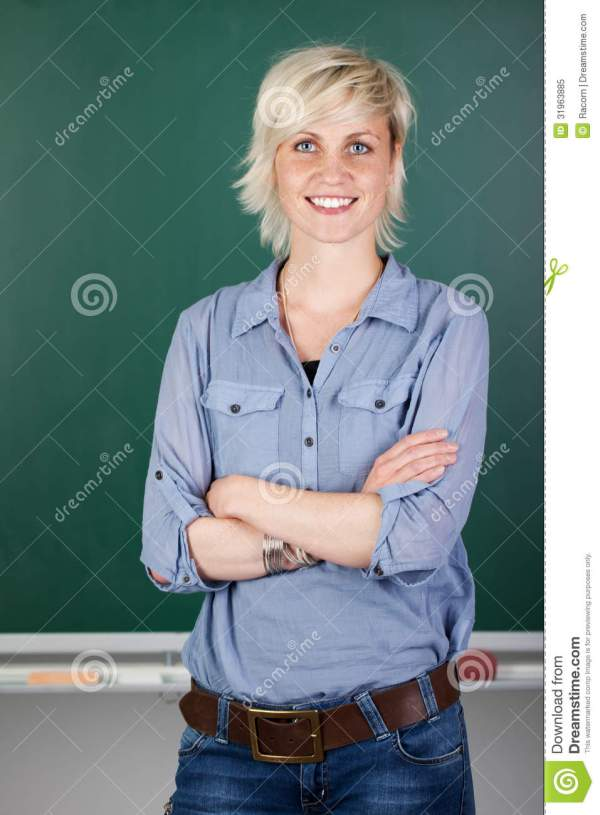 Confident Female Teacher In Front Of Chalkboard Royalty