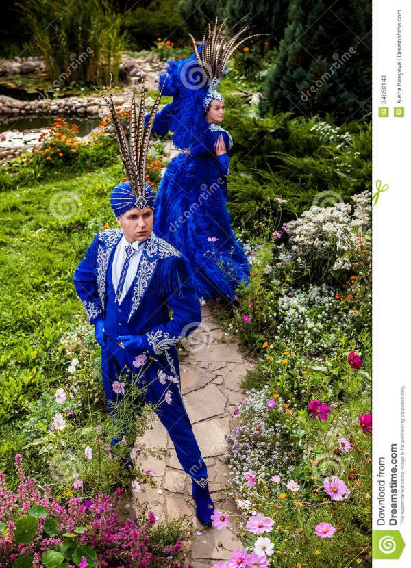Couple In Expensive Dark Blue Costume Of Illusionist Pose Fairy Tale Flowers Park. Stock