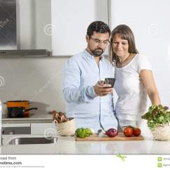 Kitchen Phone Shoes For Work In The Couple Looking At A Mobile Stock Image Of Cooking And