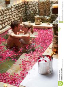 Couple Relaxing In Flower Petal Covered Pool Stock