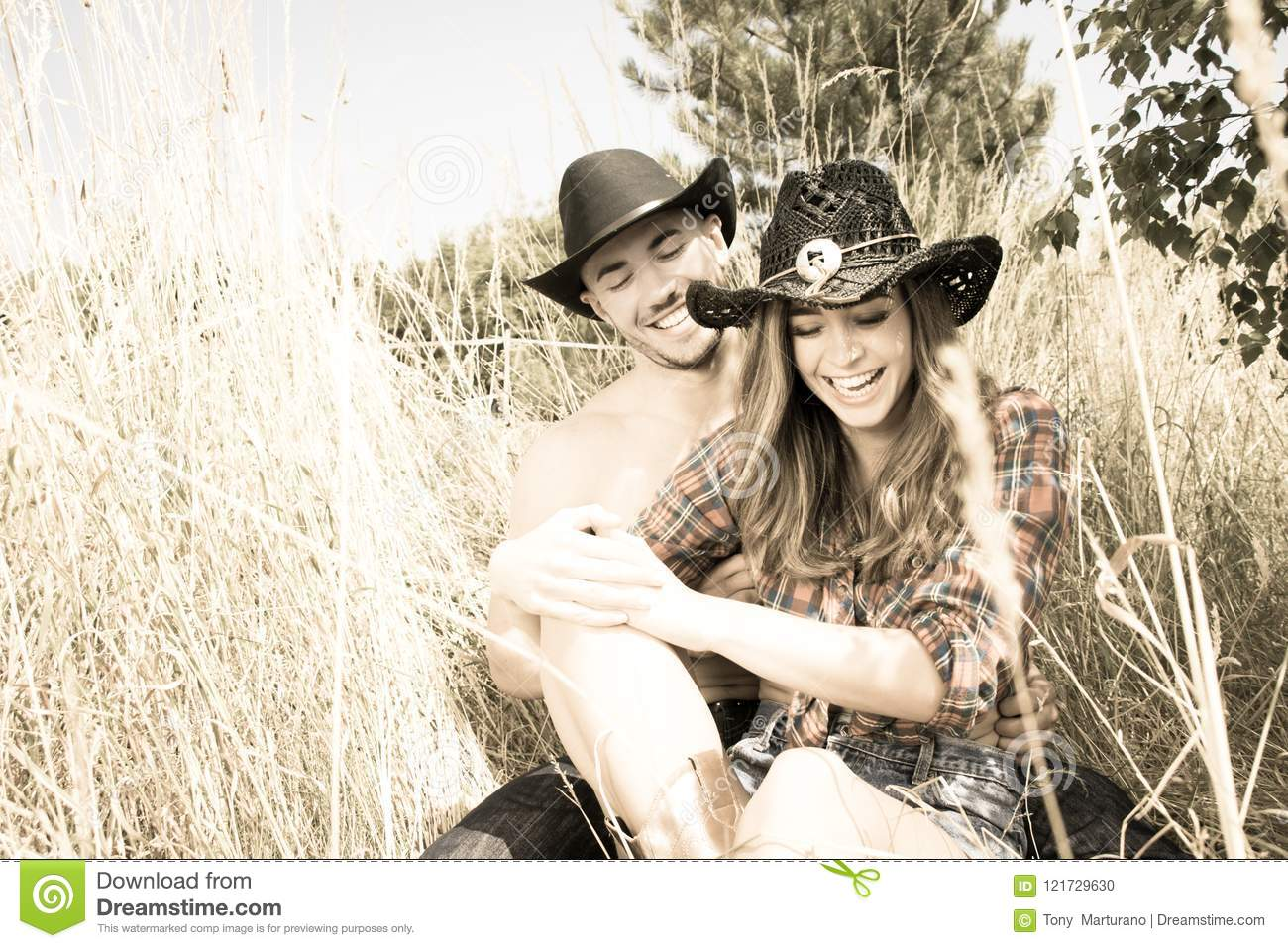 Cowboy And Cowgirl Couple Sitting In Grass Laughing As