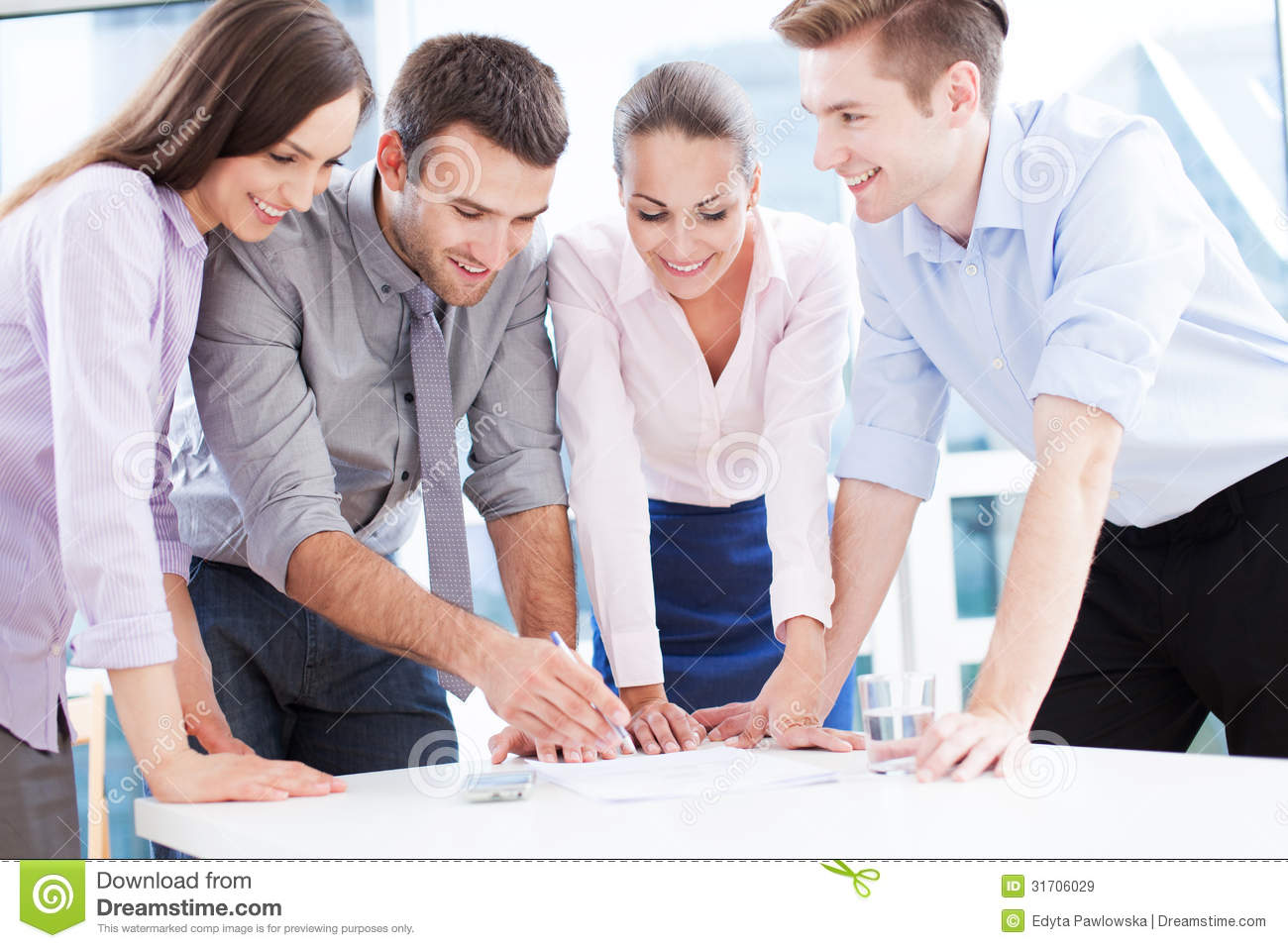 Coworkers Leaning Over Table Royalty Free Stock Images