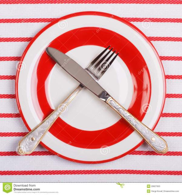 Crossed Knife And Fork On A Red Plate On Striped
