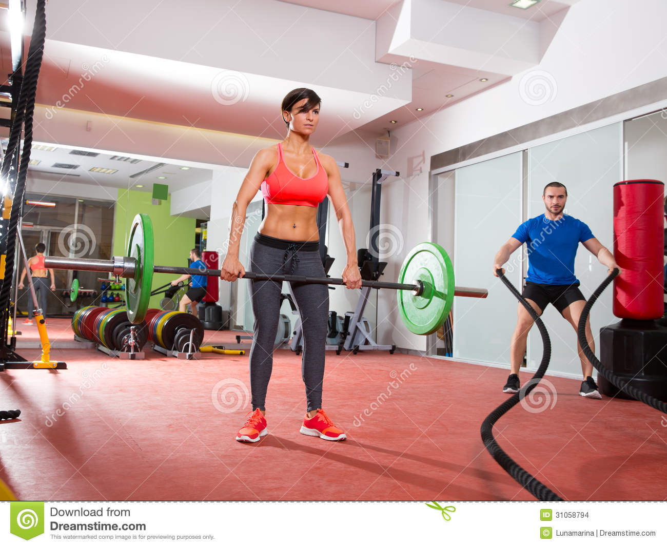 crossfit fitness gym weight lifting bar women and men battling ropes