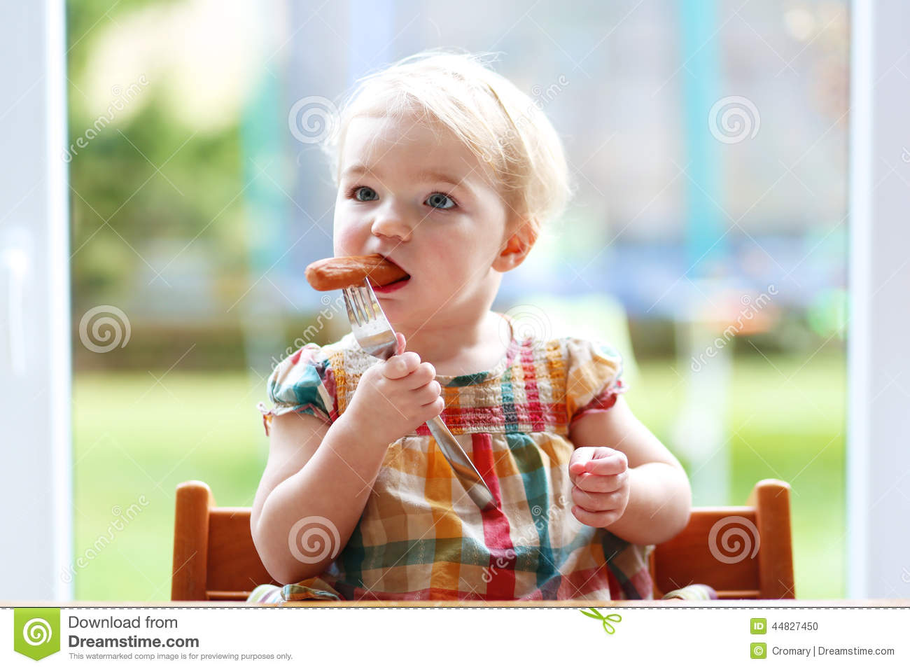 baby high chair for eating swivel vanity cheap cute girl sausage from fork stock photo - image: 44827450