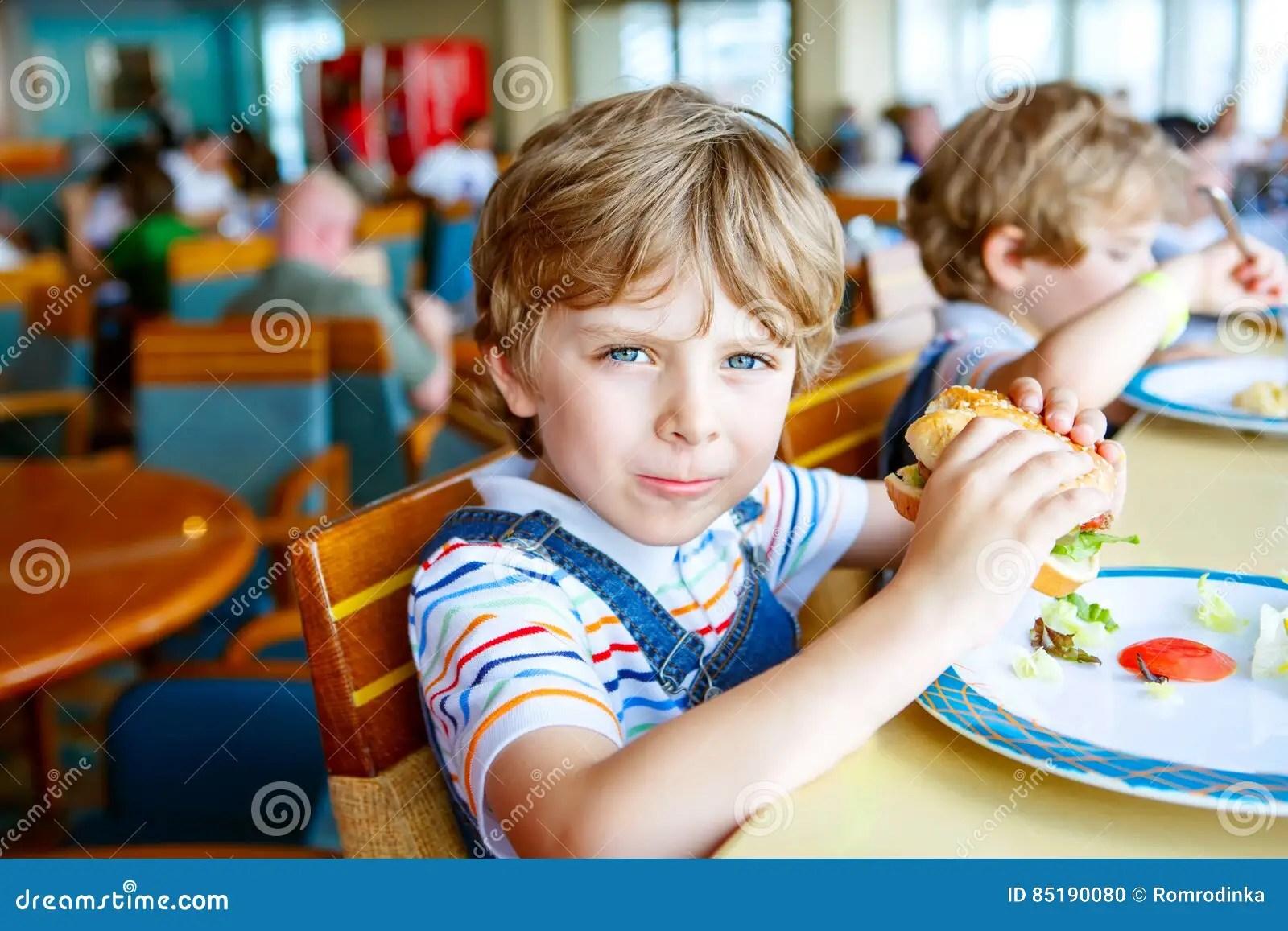 Cute Healthy Preschool Boy Eats Hamburger Sitting In