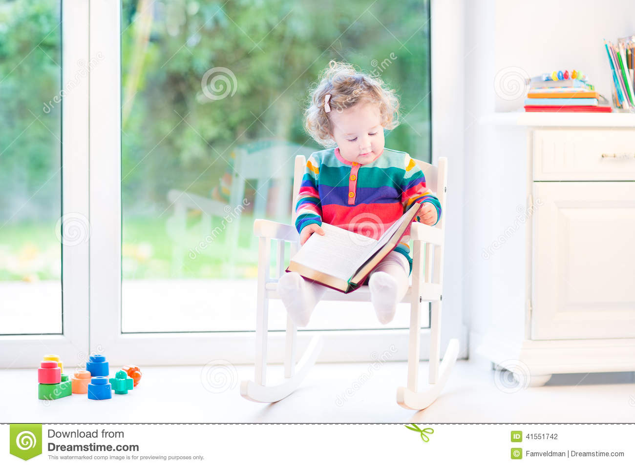 chair for toddler girl egg swing rural king cute reading a book in rocking stock photo