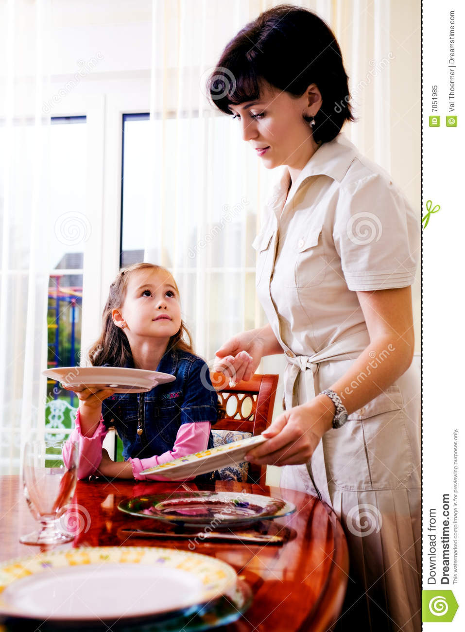 Daughter And Mom Setting The Table Royalty Free Stock