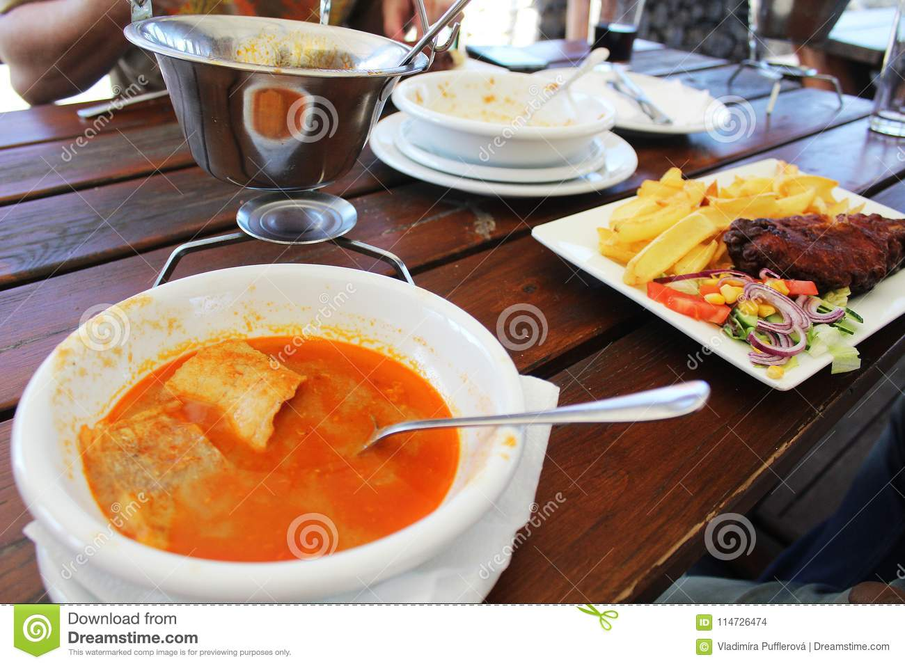 Dinner At Restaurant - Hungarian Fish Soup Named Halaszle And Fried Hake With French Fries And Vegetables Stock Photo - Image of entertainment ...