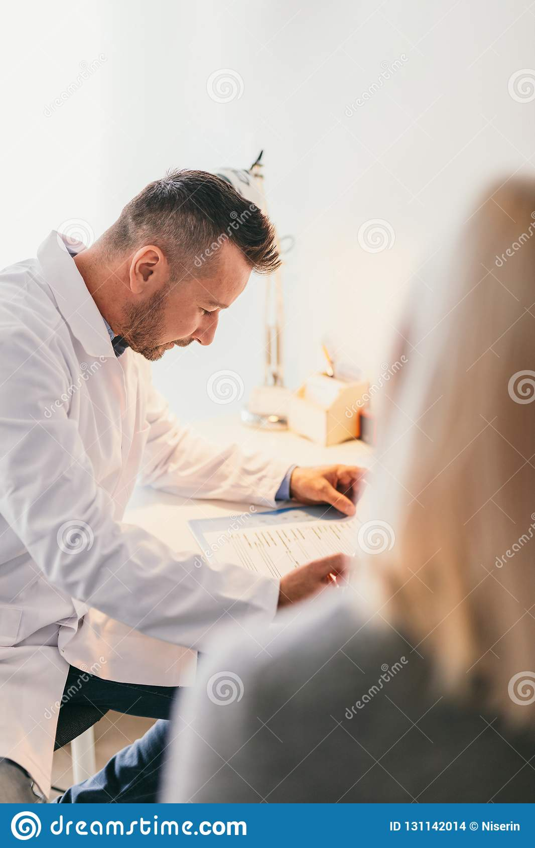 Doctor Filling A Blank Form With A Patient Stock Photo