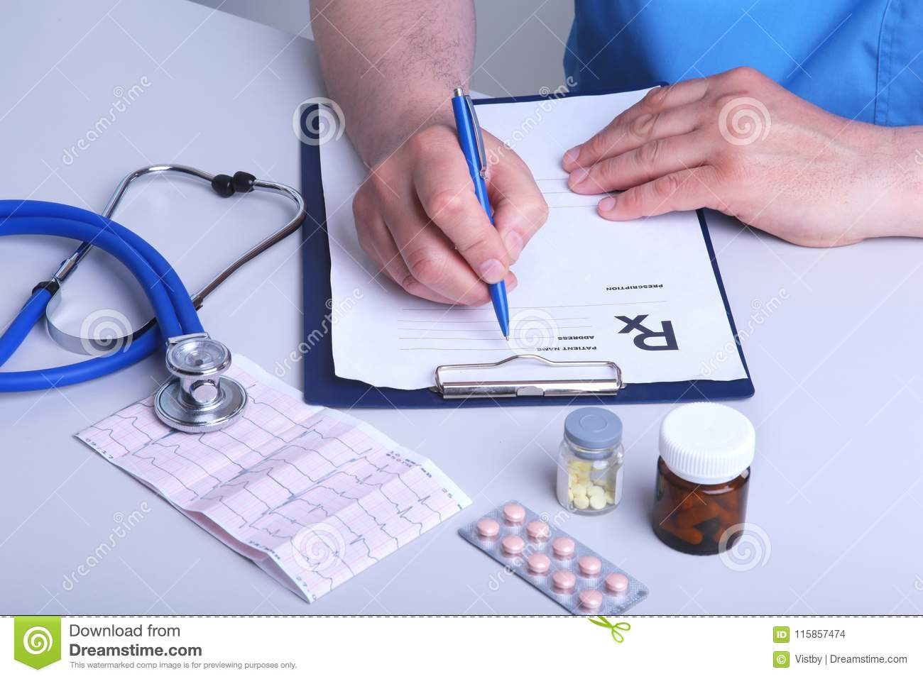 hight resolution of the doctor holds a blister with pills in his hand and writes out the prescription in