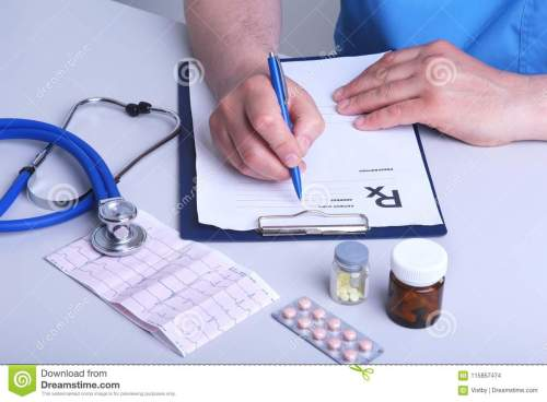 small resolution of the doctor holds a blister with pills in his hand and writes out the prescription in