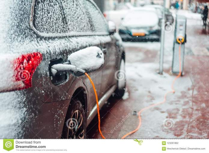 electric car plug charging in the winter stock photo - image of