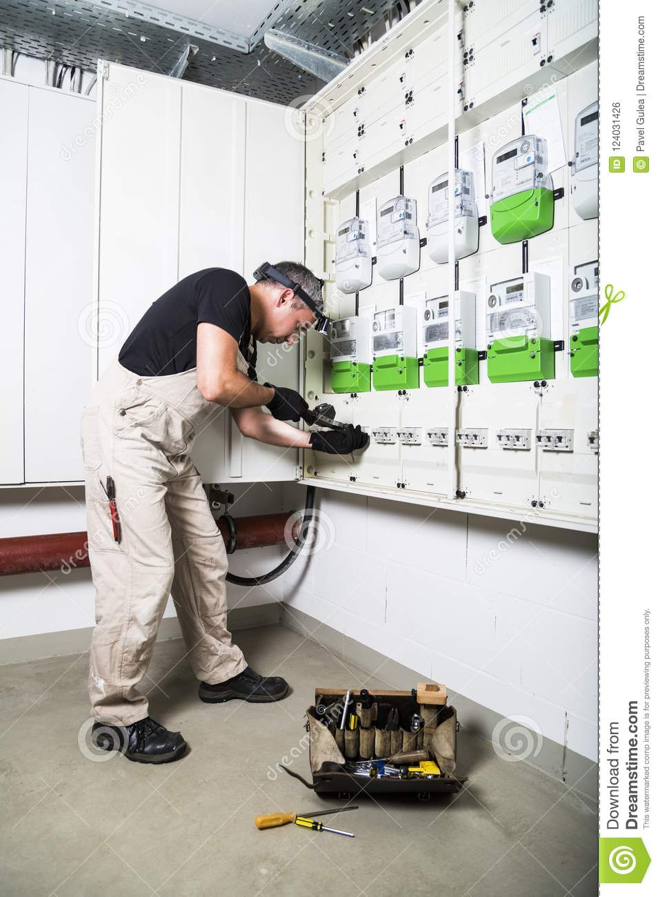 hight resolution of electrician standing near fuse box or switch box and testing equipment with retro voltmeter box of electrician tools stands near