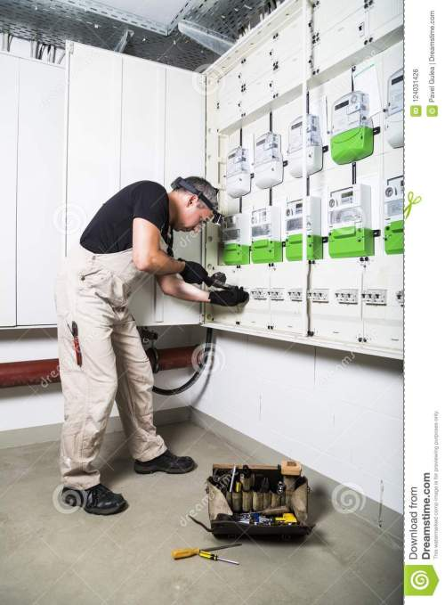small resolution of electrician standing near fuse box or switch box and testing equipment with retro voltmeter box of electrician tools stands near