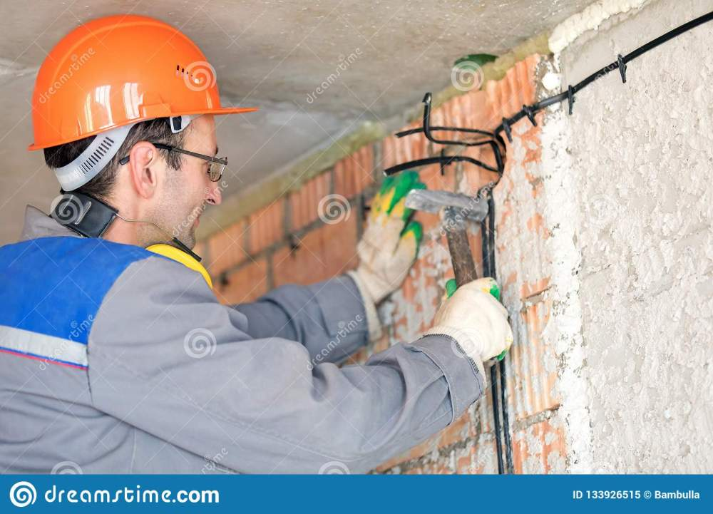 medium resolution of electrician man construction worker installing fuse box electrical cable at house wall