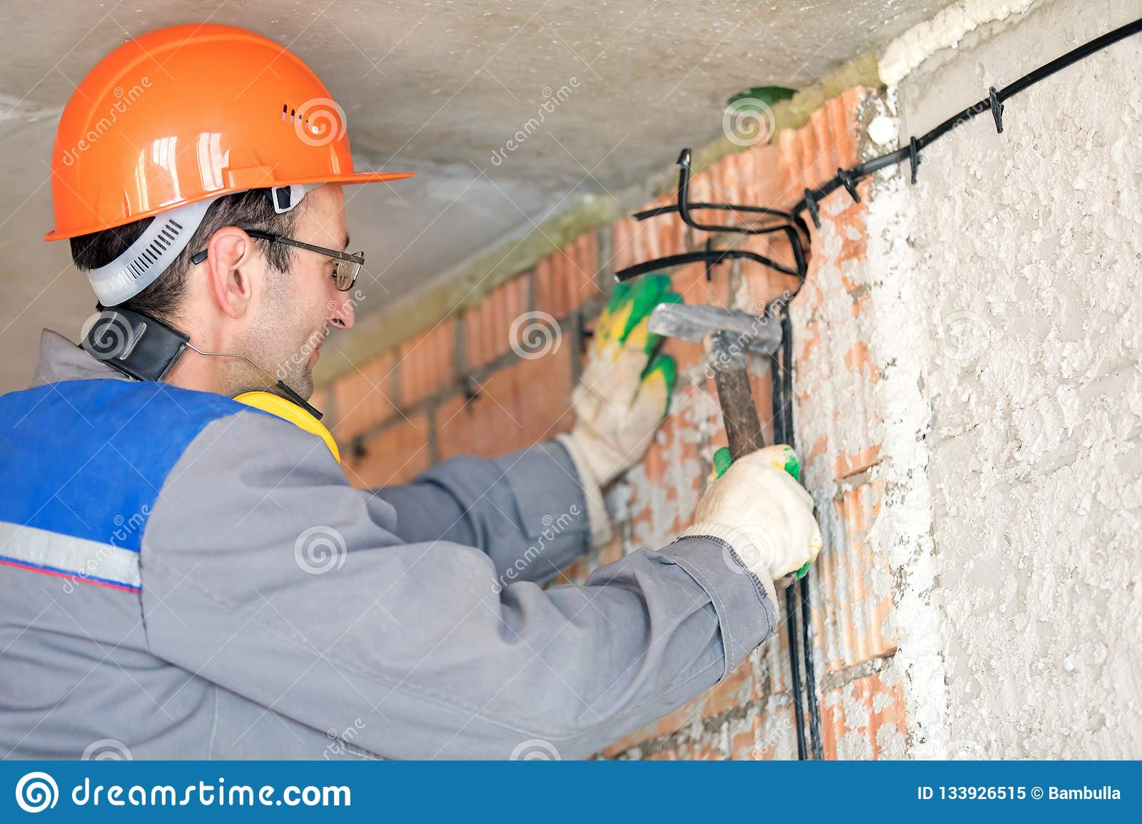 hight resolution of electrician man construction worker installing fuse box electrical cable at house wall