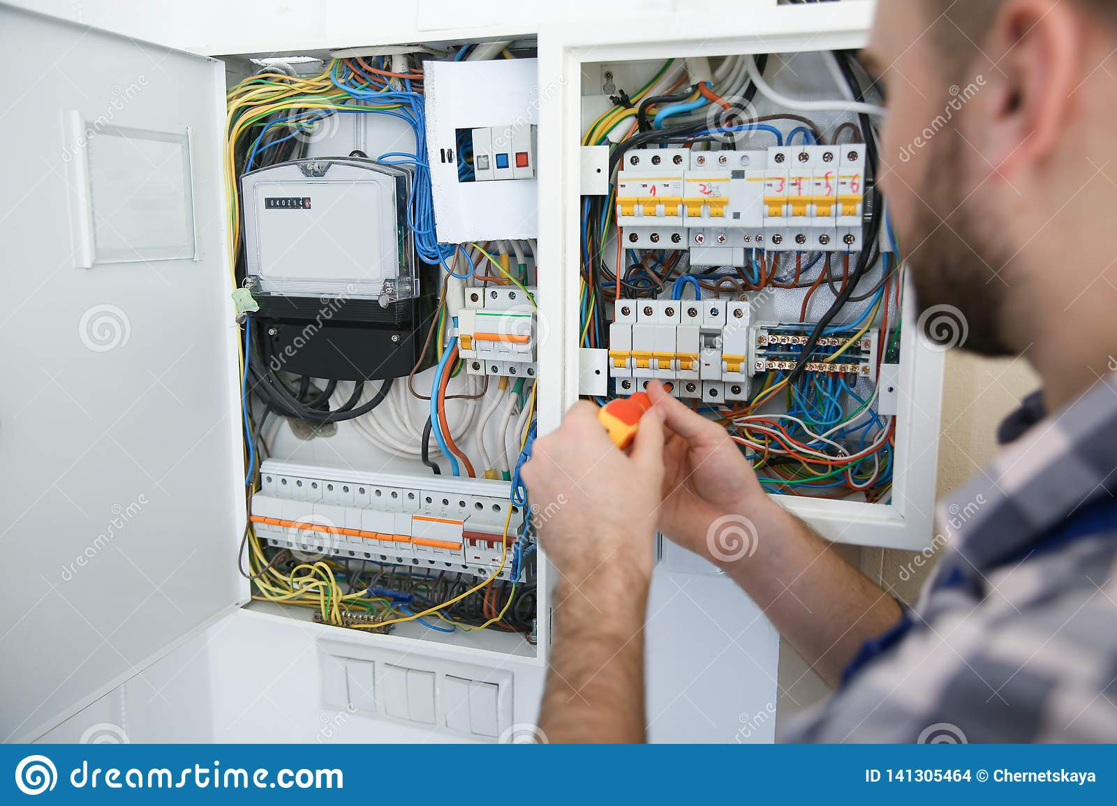 hight resolution of electrician repairing fuse box with screwdriver indoors