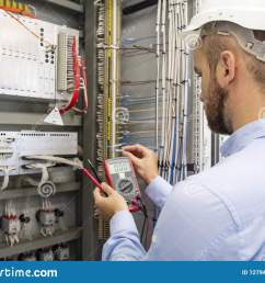 electrician technician in fuse box maintenance engineer in control panel worker is testing automation [ 1600 x 1156 Pixel ]