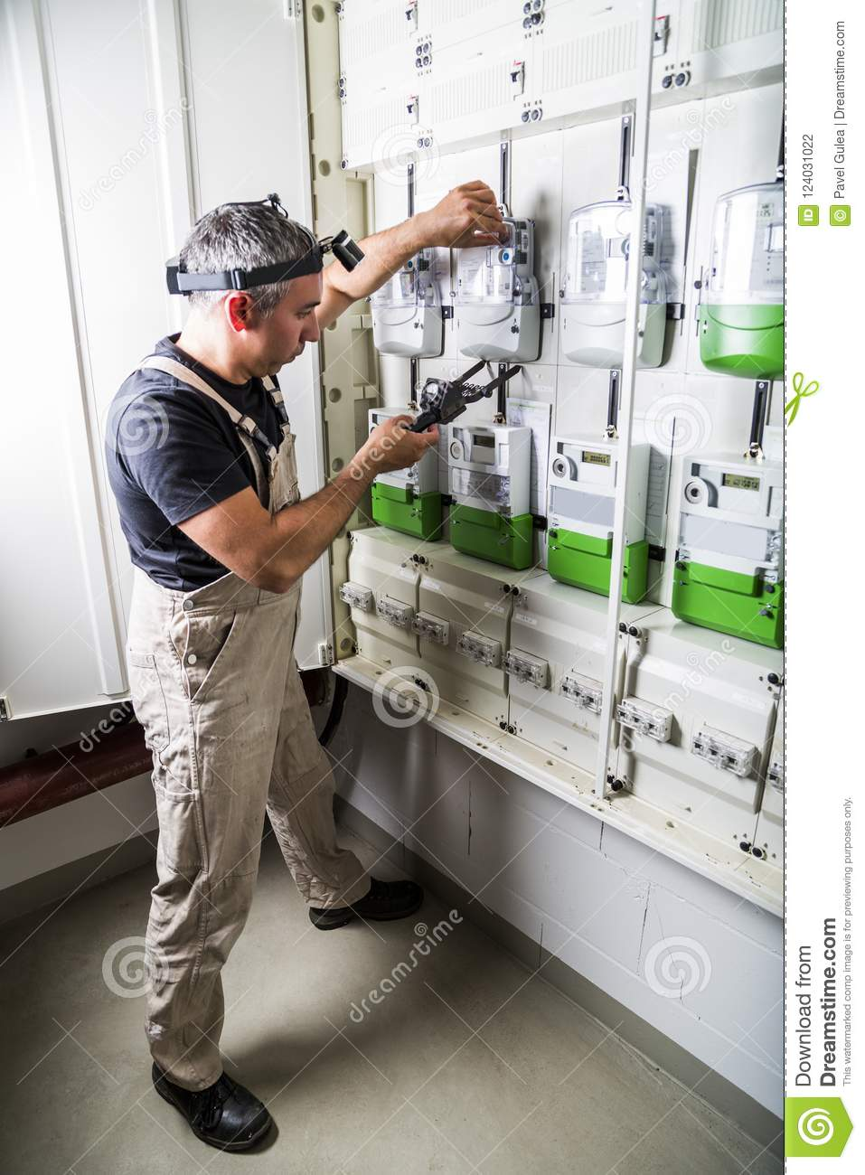 medium resolution of electrician standing near fuse box or switch box and testing equipment with old retro voltmeter