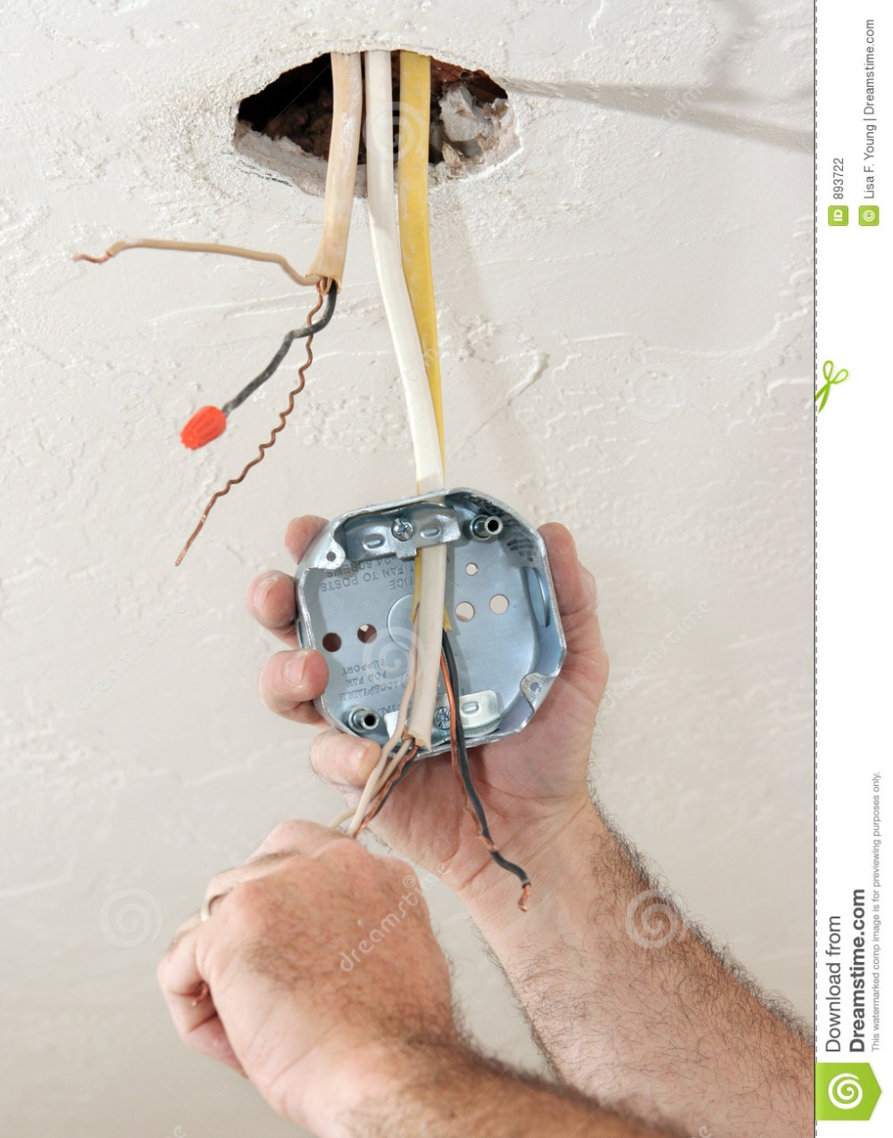 medium resolution of an electrician threading wire through a regulation fan ceiling box work being performed to code by licensed master electrician