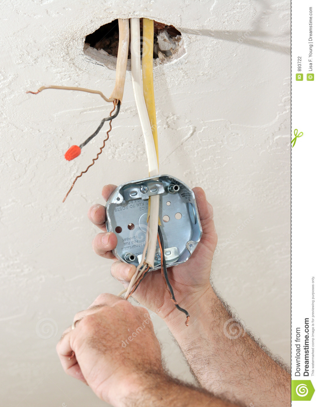 hight resolution of an electrician threading wire through a regulation fan ceiling box work being performed to code by licensed master electrician