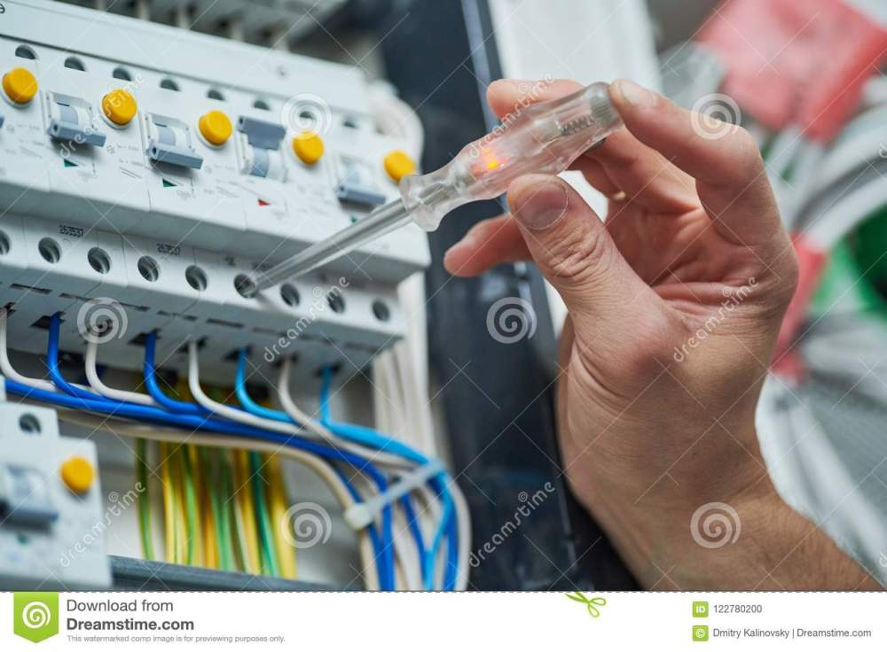 medium resolution of electrician works with electric meter tester in fuse box