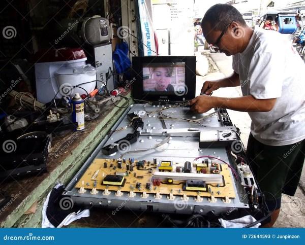 An Electronics Repair Shop Technician Works On A Flat ...