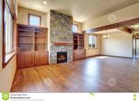Empty Living Room With Hardwood Floor, Stone Fireplace And