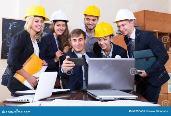 Engineers Posing In Front Of Smartphone Stock