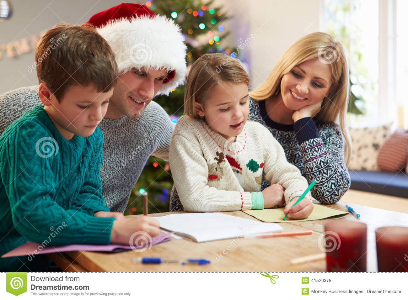 Family Writing Christmas Cards Together Stock Photo