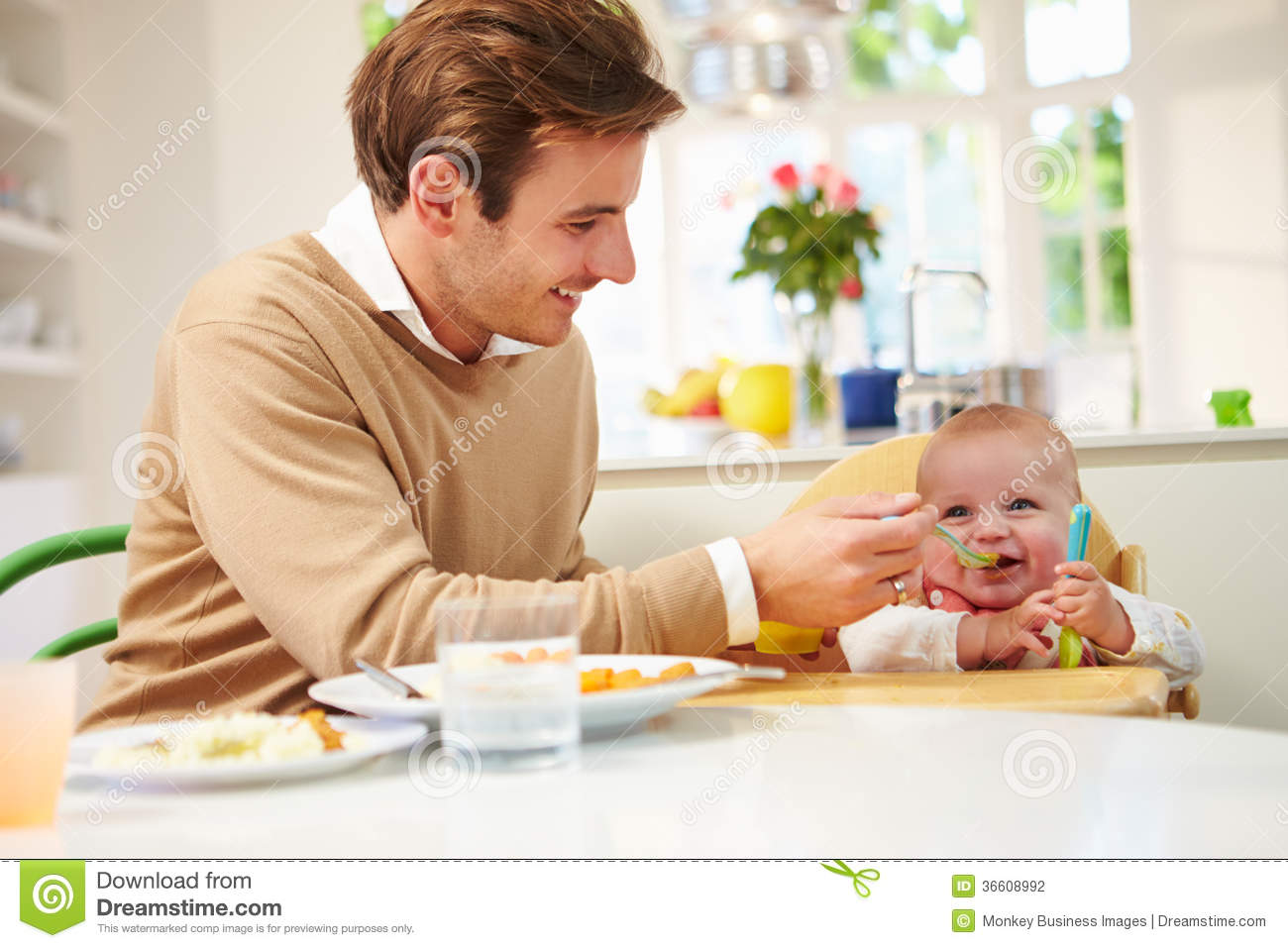 Baby Food Chair Father Feeding Baby Sitting In High Chair At Mealtime