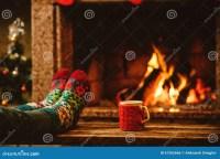 Feet In Woollen Socks By The Christmas Fireplace. Woman ...