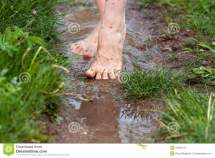 Feet Of Young Woman Walking Puddles