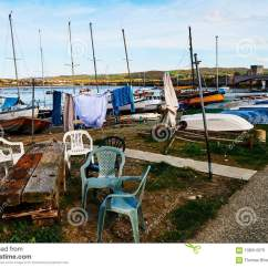 Fishing Chair Setup Clear Plastic Desk Seating In Harbour Fisherman Boat Village Wales Uk England Cloudy Sky And Green Hills