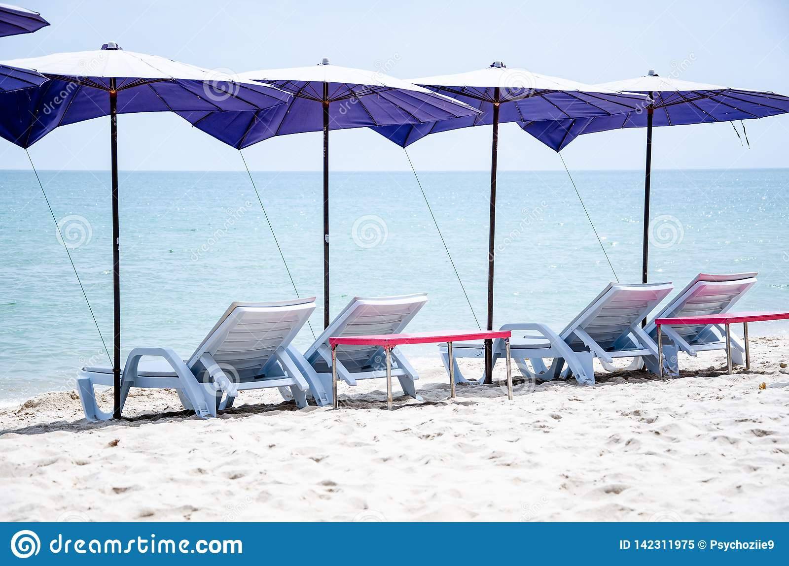 Sunbathing Chairs Folding Chairs With Umbrellas Are Located On The Beach For