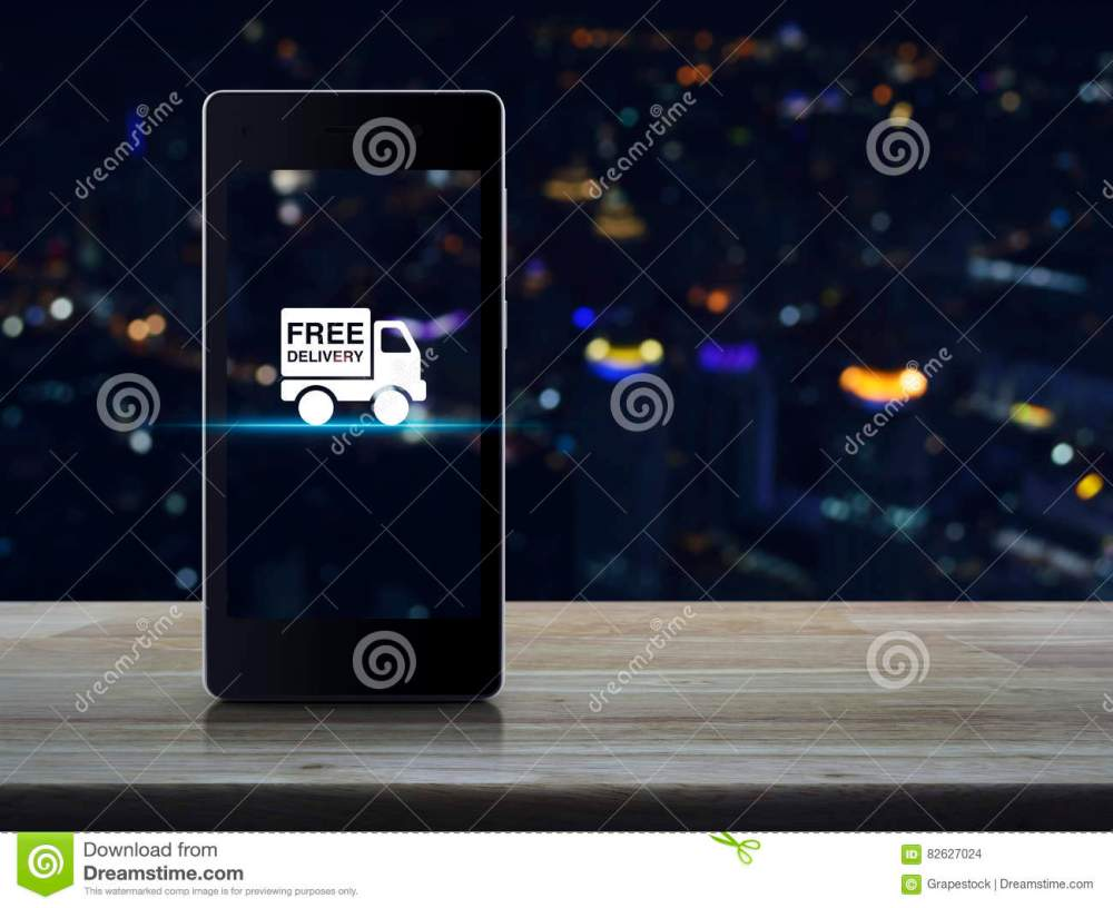 medium resolution of free delivery truck icon on modern smart phone screen on wooden table in front of blurred light city tower transportation business concept