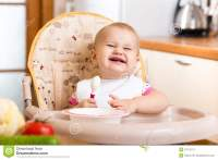 Funny Baby Eating In High-chair On Kitchen Royalty Free ...