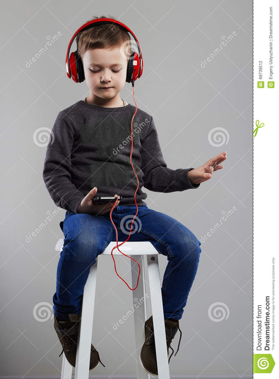Funny Child.little Boy In Headphones Sitting On Chair
