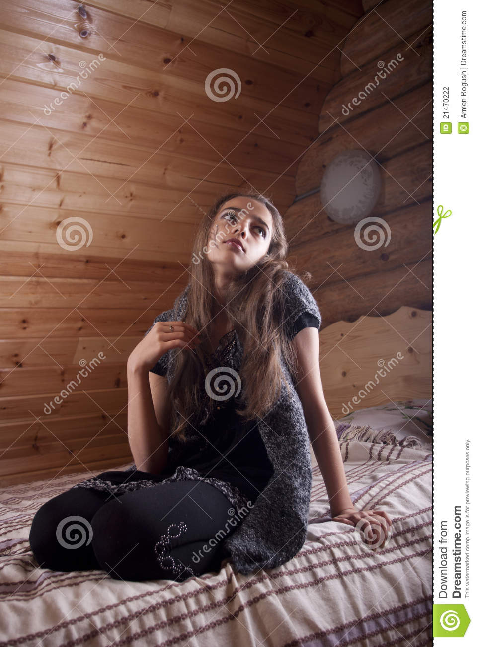 Girl In Black Jersey Sitting On Bed Stock Photo  Image