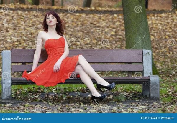 Girl In Elegant Red Dress Sitting Bench Autumnal