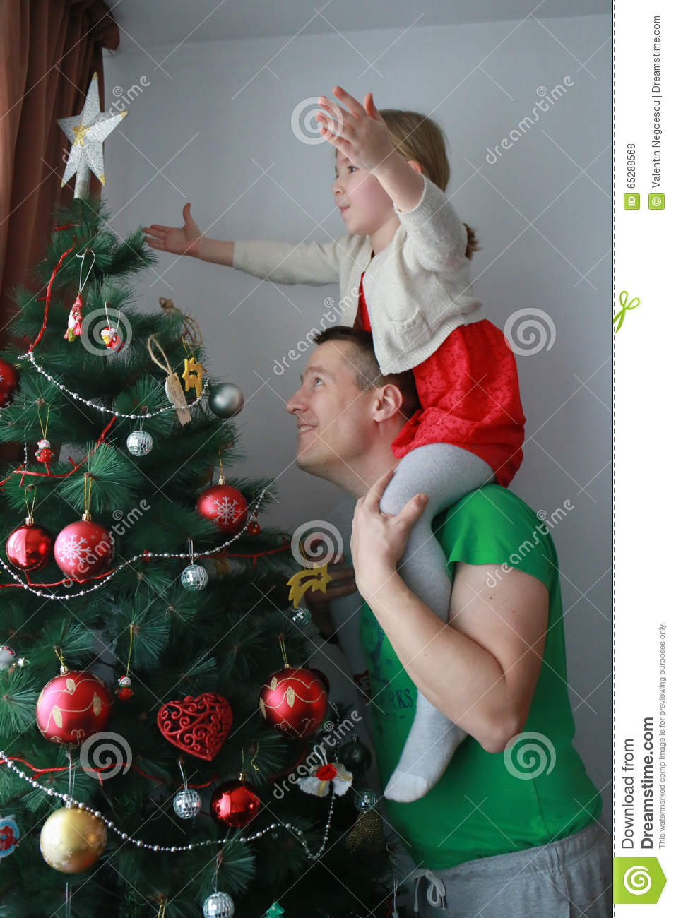 The Girl Put The Christmas Star On Top Of The Tree Stock Photo  Image of adult cute 65288568