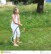 Girl In White Splashing With Garden Hose