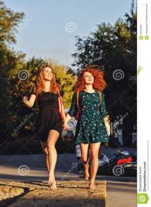 Girlfriends Walking In Park Barefoot. Stock