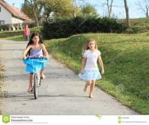 Girls Running And Riding Bike Stock - 34585683
